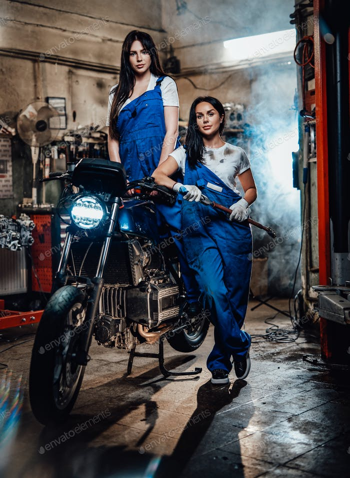 Two brunette women in blue overalls posing next to a custom bobber in authentic workshop garage