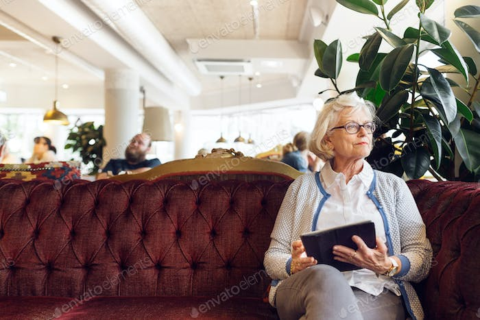 Senior woman with digital tablet sitting on sofa and looking away