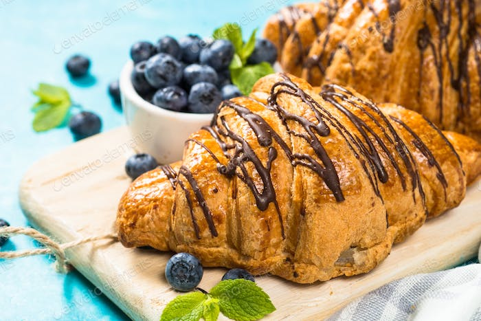Croissant with fresh berries on blue