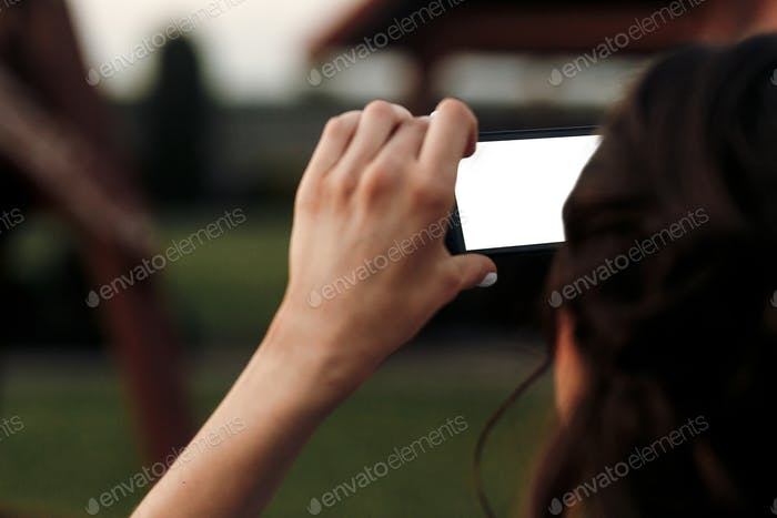 woman holding smart phone with empty screen and taking photo at wedding reception