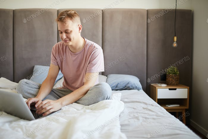 Young relaxed businessman in t-shirt networking in bed