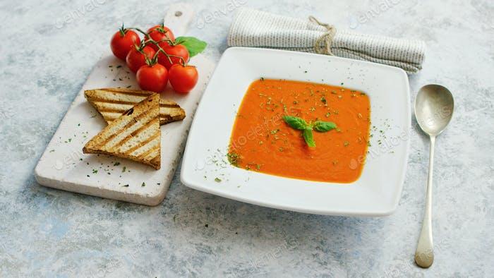 Tomatensuppe serviert mit knusprigem Brot