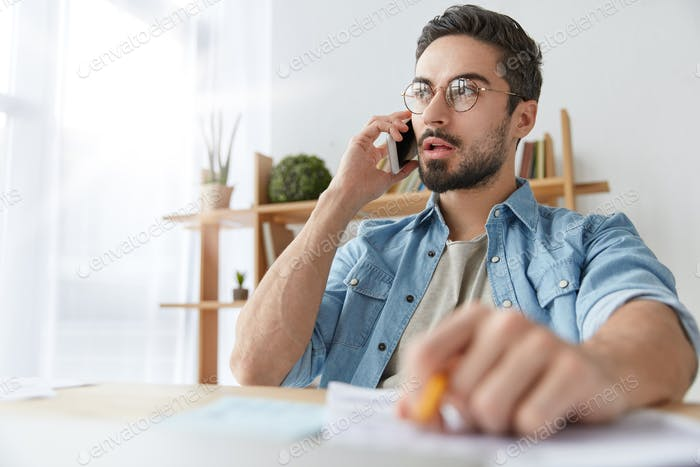 Serious concentrated fashionable male office worker calls to colleague on cellular, has phone talk,