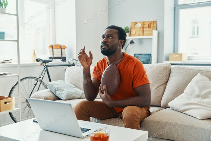 Young African man feeling excited about game while watching sport match at home