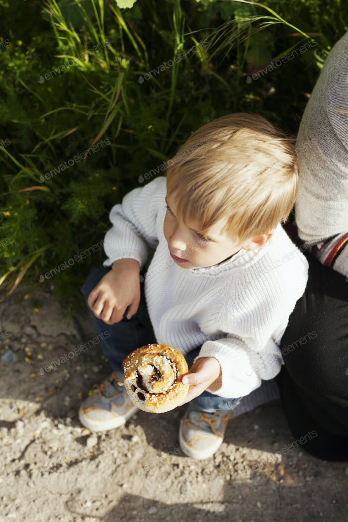 High angle view of boy holding cinnamon bun by mother at field