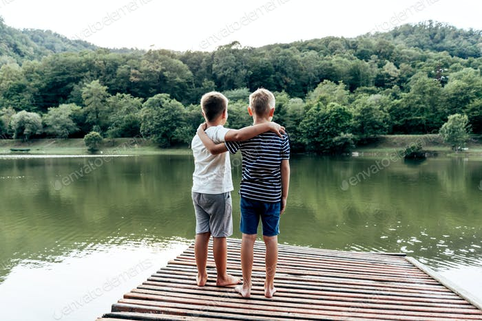Two boys stand on the pier by the lake. Children's male friendship. Summer in the countryside.