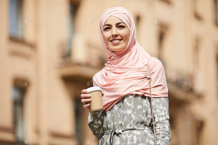 Glückliche mittelöstliche Geschäftsfrau mit Kaffeetasse