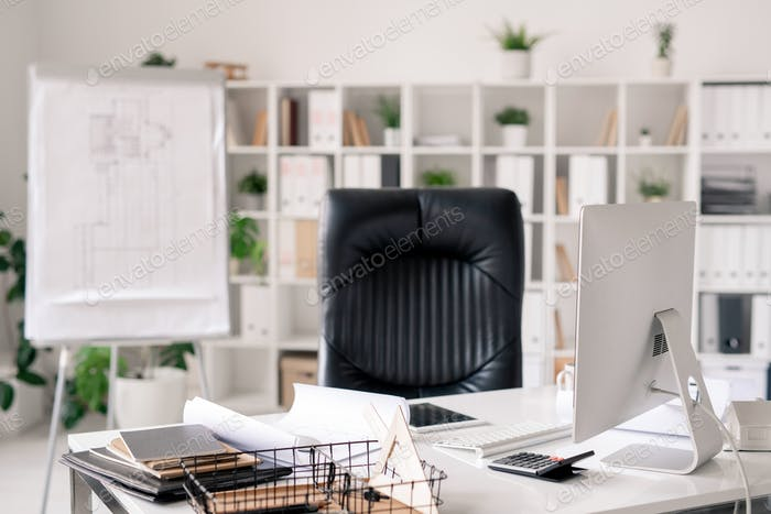Workplace with desk, black leather armchair, whiteboard, computer monitor