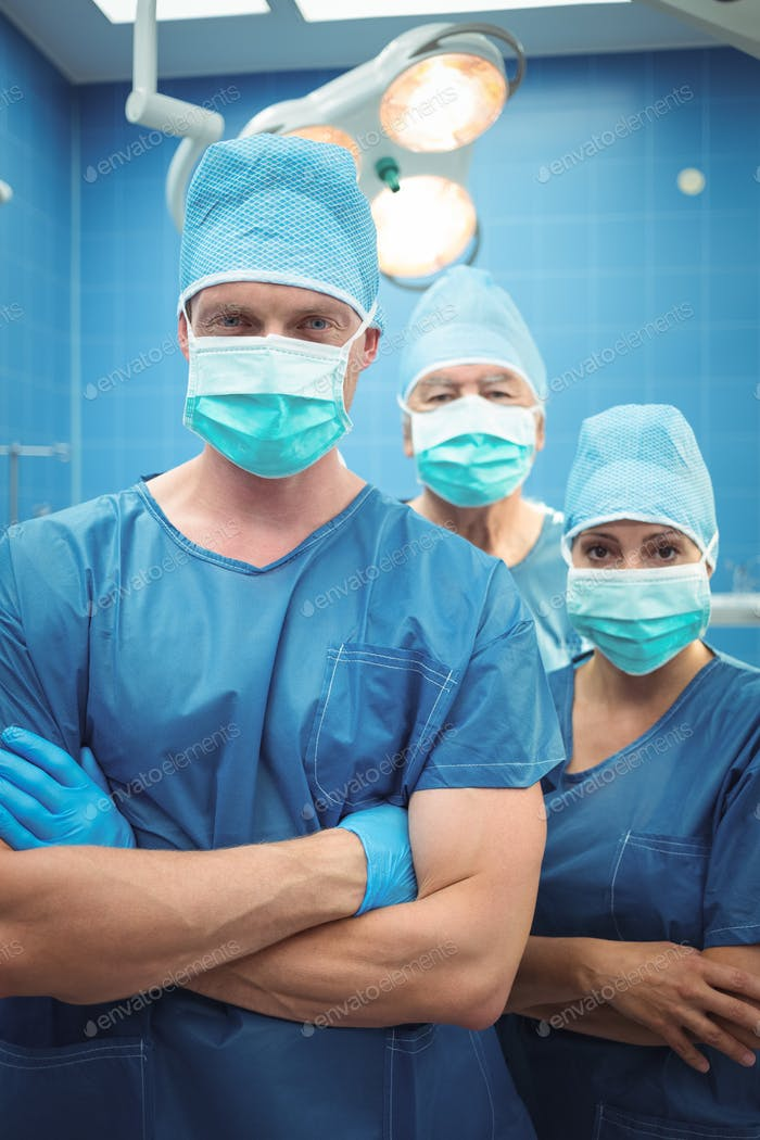 Team of surgeons standing in operation theater