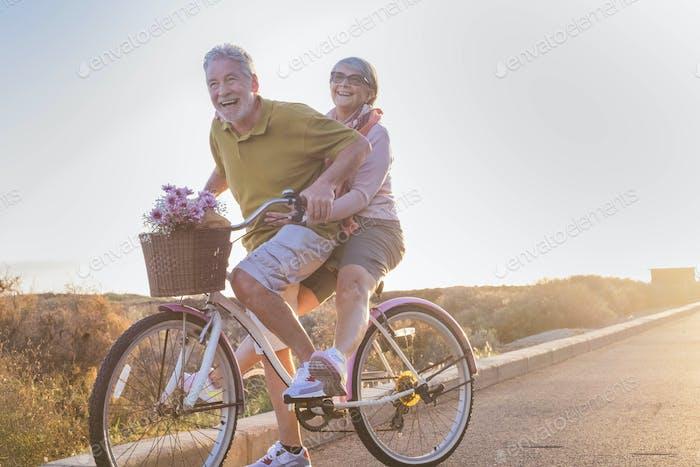 радость и счастье для взрослой супружеской пары начать и весело провести время, путешествуя на одном велосипеде на открытом воздухе