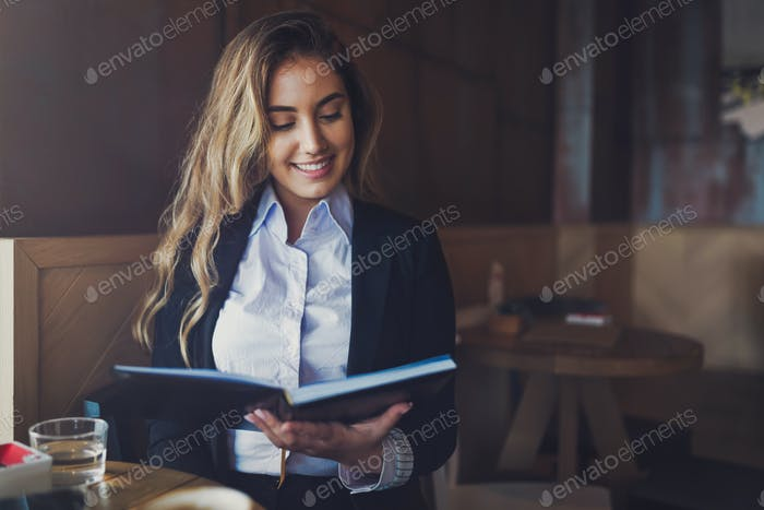 Beautiful woman reading notebook