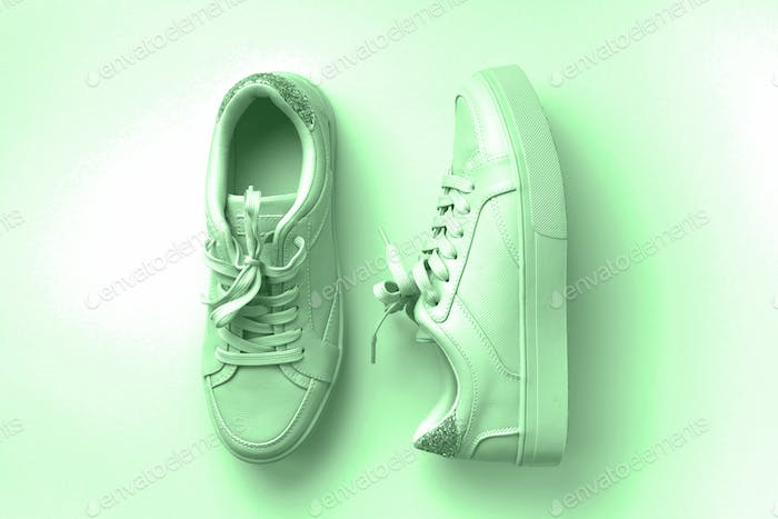White leather sneakers on mint background. Pair of fashion trendy white sport shoes or sneakers with