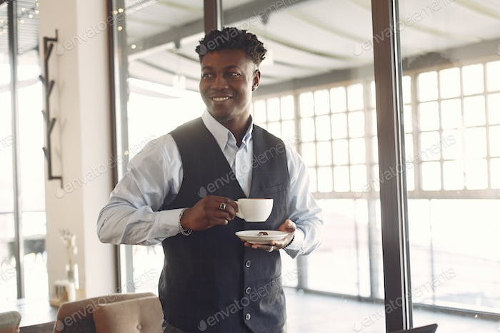 Black man in a blue shirt standing in a cafe