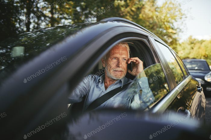 Senior man sitting in his car talking on a cellphone