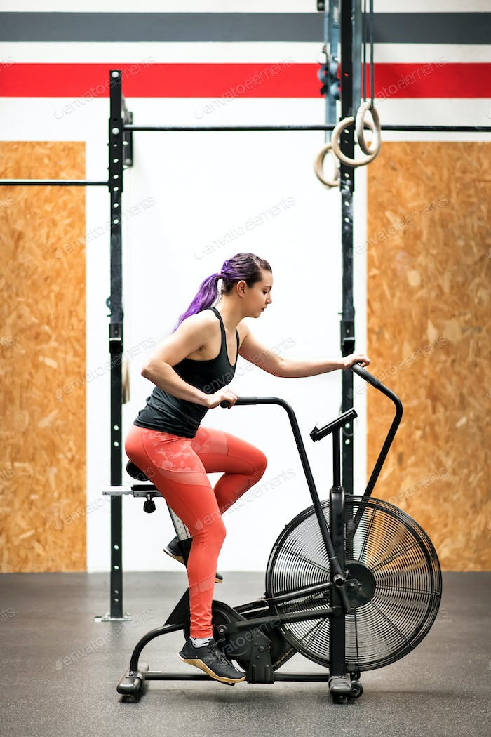 Fit young woman working out on an exercise bike