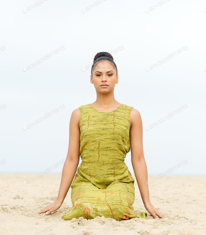Attractive young woman sitting alone at the beach