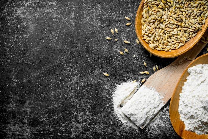 Mehl und Getreide in Schalen mit Holzspatel.