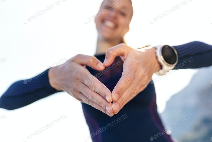 Sporty young woman making heart shape with hands while posing to