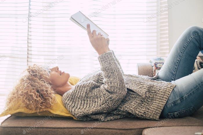 Hermosa mujer de mediana edad se acostó en el sofá en casa