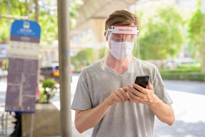 Young man using phone at the bus stop with mask and face shield for protection from corona virus