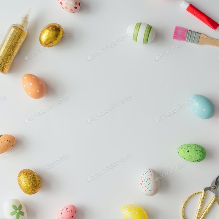Creative Easter layout made of colorful eggs, gold glitter, brush and paint. Flat lay background.