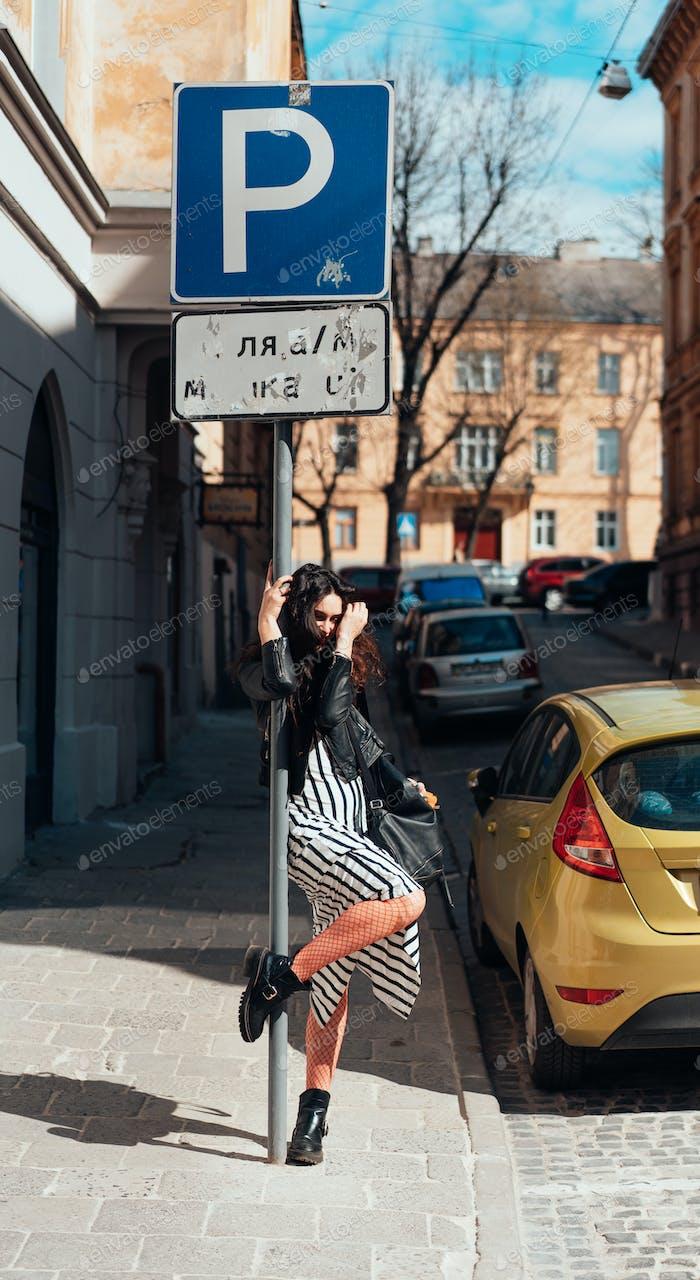 Beautiful fashionable lady posing on old street