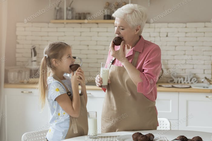 Together time of granny and her granddaughter enjoying fresh muffins in kitchen