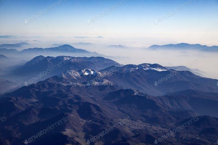 Luftbild der schneebedeckten Alpen.