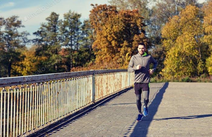happy young man running over city bridge