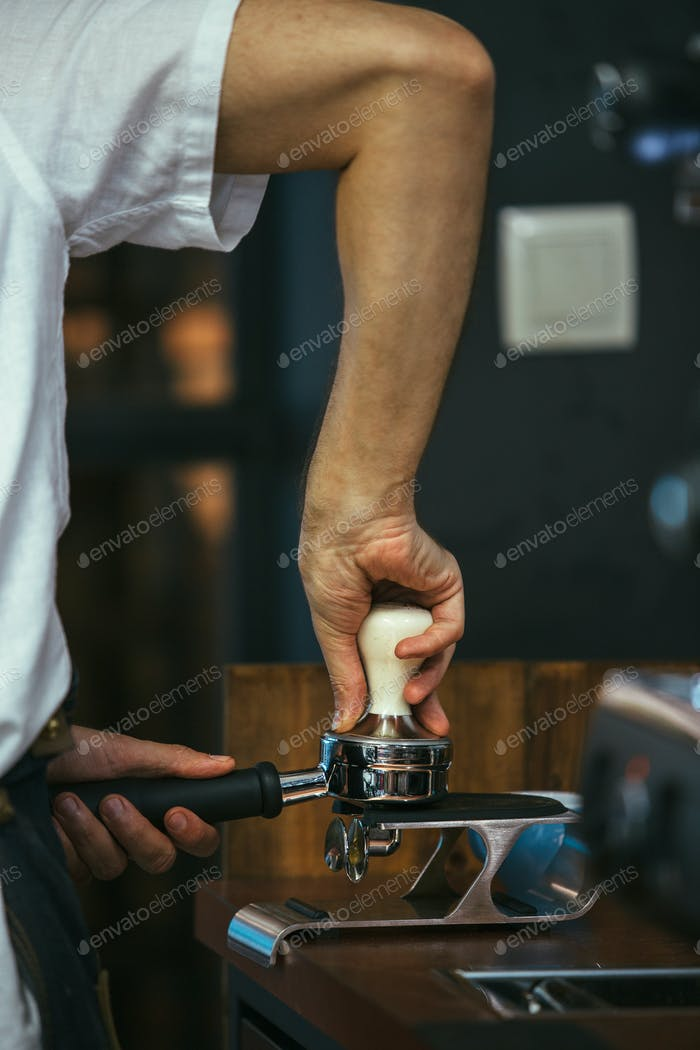 Barista pressing ground coffee with tamper