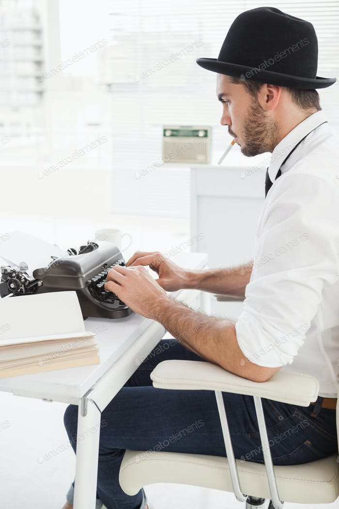 Hipster businessman using a typewriter in his office