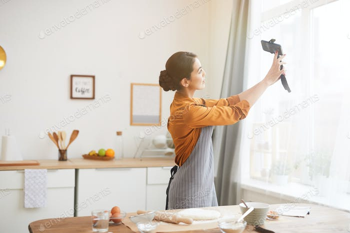 Young Woman Filming Vlog in Kitchen