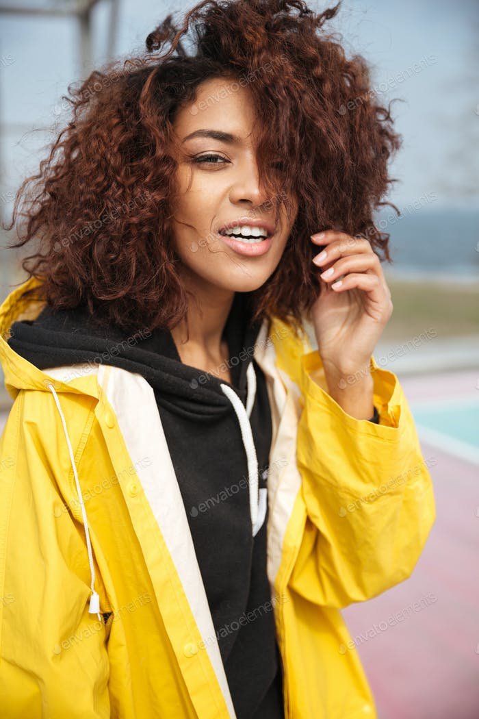 Amazing african curly young woman wearing yellow coat
