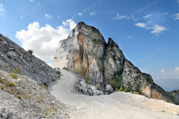 Road winding past an excavated mountain peak