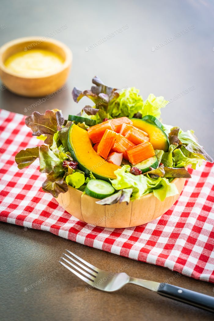 Crab sticks meat with fresh vegetable salad with mayonnaise sauc