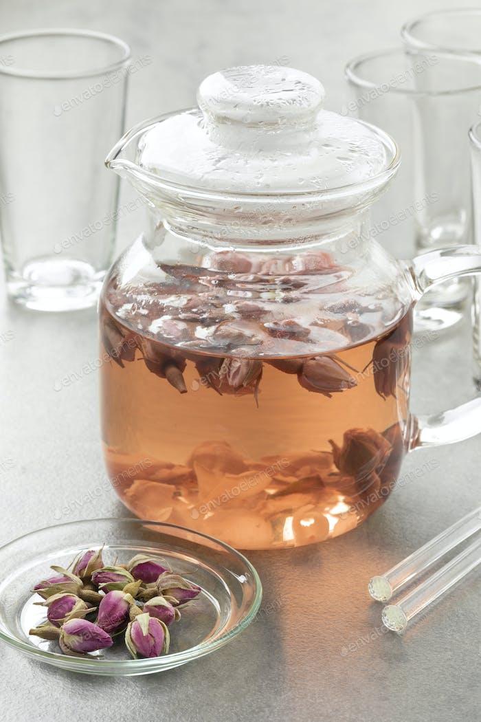 Glas-Teekanne mit getrockneten Rosenknospen Tee als Heißgetränk