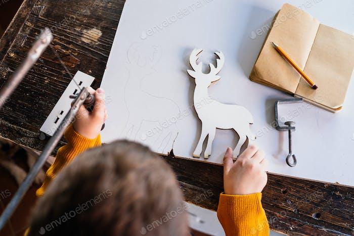 Making wooden deer figurine