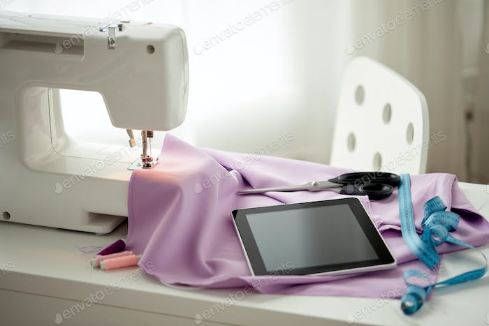 sewing machine, tablet pc, scissors and ruler