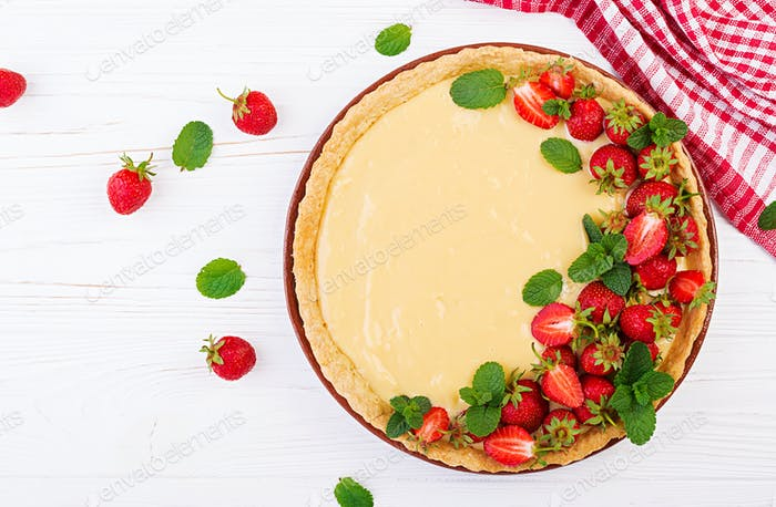 Tart with strawberries and whipped cream decorated with mint leaves on light background. Top view