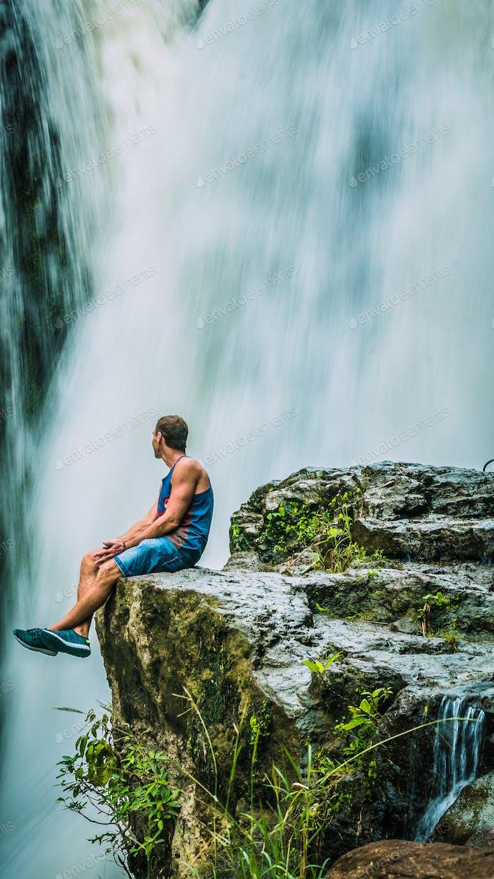 Man sitting in Front of Tegenungan Waterfall near Ubud in Bali, Indonesia