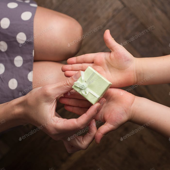 Mother giving a small gift to her kid with open hand