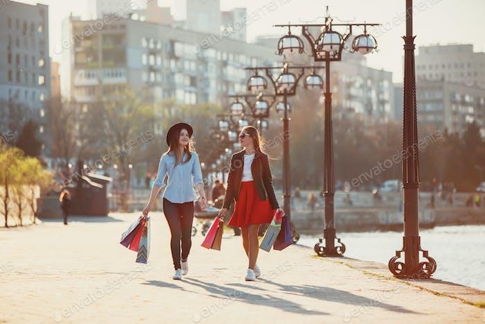 Zwei Mädchen zu Fuß mit Einkaufen auf Straßen der Stadt