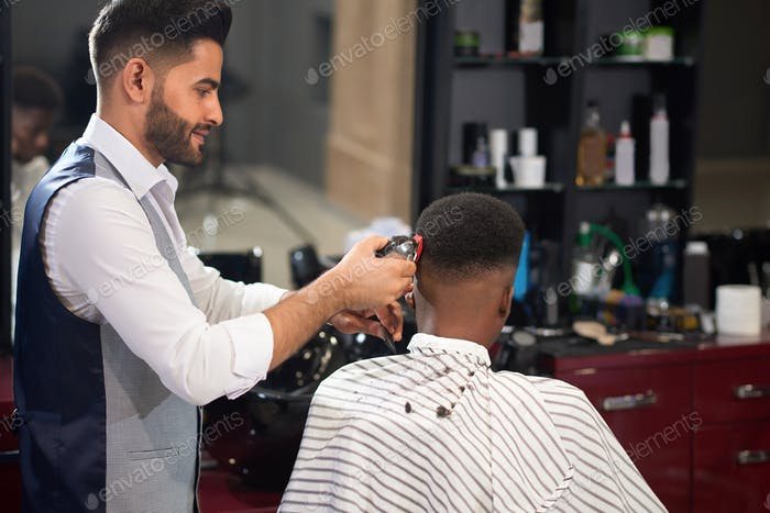 Barber trimming hair of male with clipper in barber shop