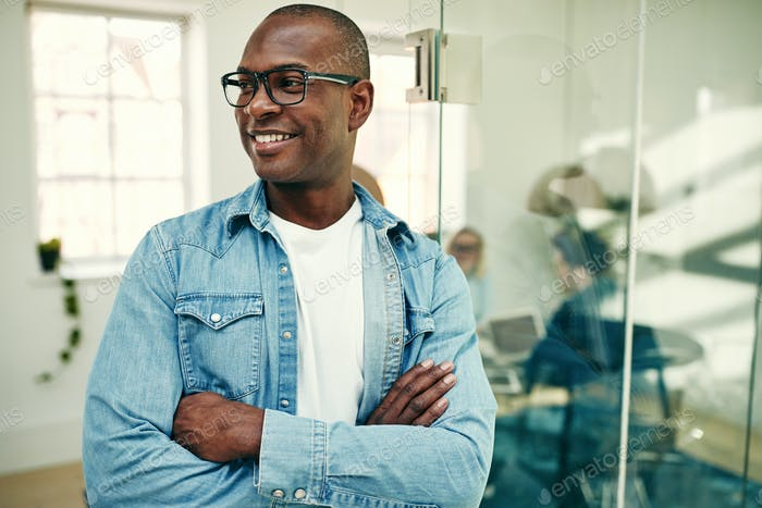Smiling young African businessman standing in a modern office