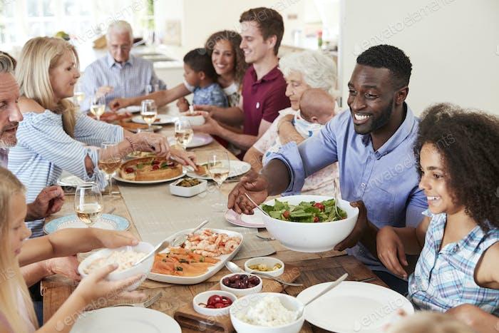 Gruppe von Familie und Freunden, die am Tisch sitzen und Essen genießen
