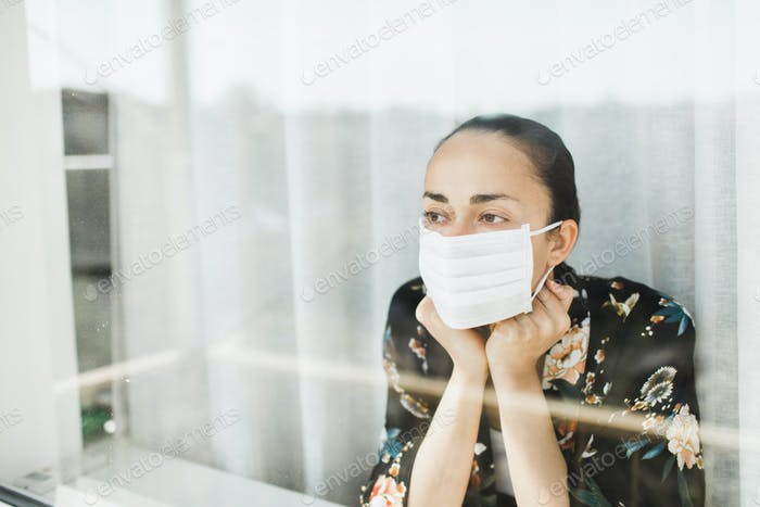 Self isolation in coronavirus quarantine. Woman in medical mask looking through window
