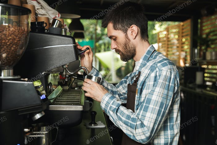 Image of professional barista man making coffee while working in