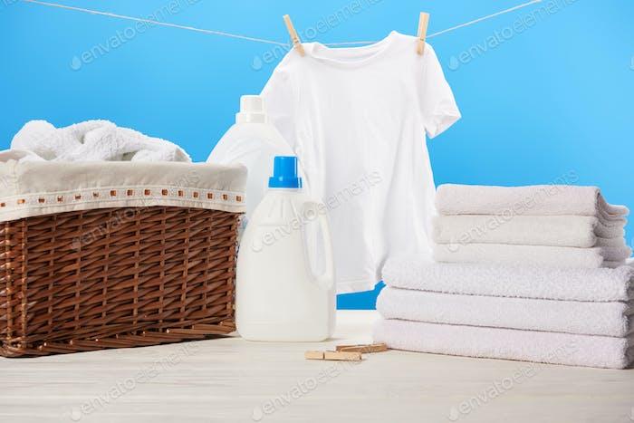 Plastikbehälter mit Wäschespülungen, Wäschekorb, Handtuchhaufen und sauberer weißer Kleidung