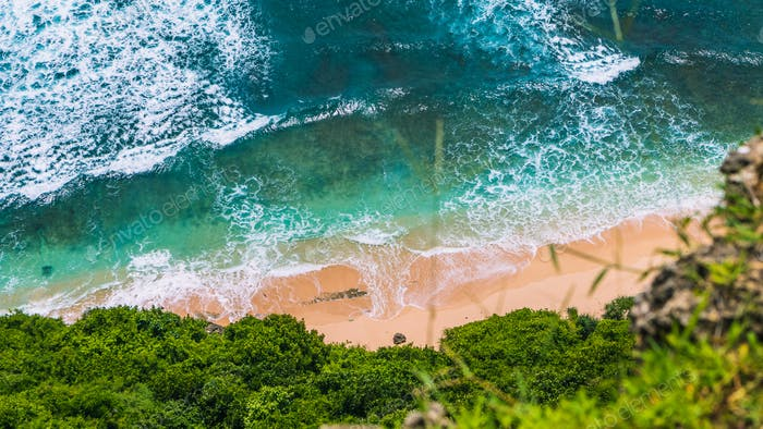 Aerial view of pure clear turquoise colored waves rolling on tropical sandy beach on sunny day