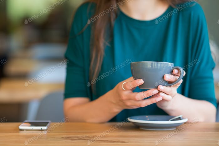 Closeup cup of coffee. Young woman in outdoor cafe